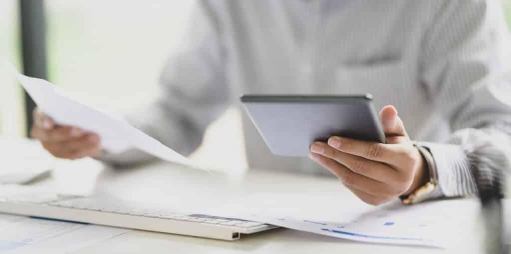 Homme travaillant comparant documents sur tablette