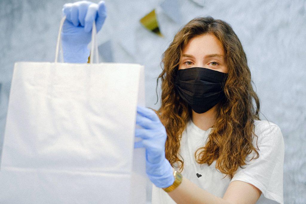 Vendeuse donnant sac de course shopping avec masque et gant de protection
