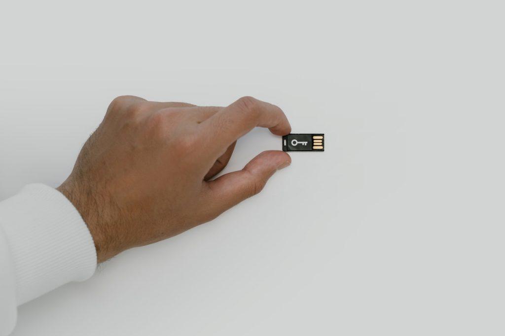 Homme tenant une petite clé usb sécurisée, cryptée