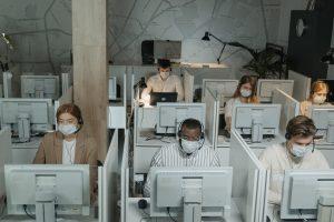 Bureau de call-center avec employés portant masque durant covid