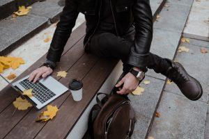 Homme assis sur un banc, regardant son ordinateur