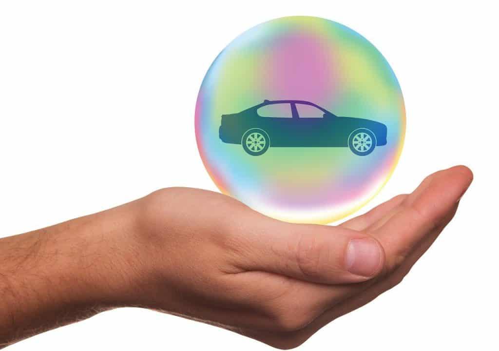 Main portant une bulle entourant une voiture pour la protéger