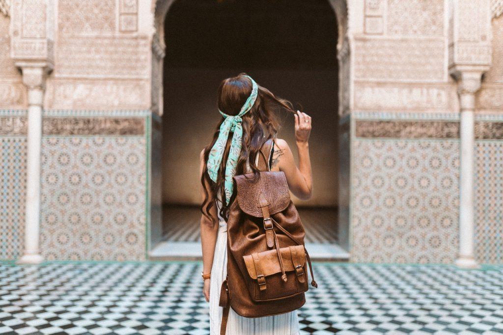 Femme devant un bâtiment marocain portant une robe bohème et un sac en cuir