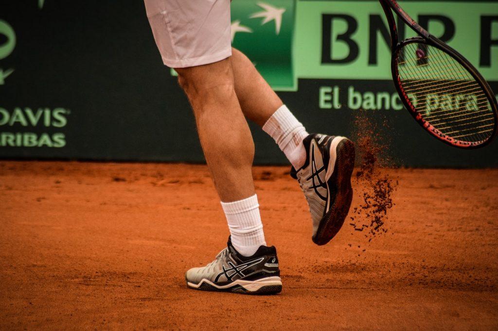 Tennisman, tapant sa raquette sur ses basket et jouant sur un terrain en terre battue