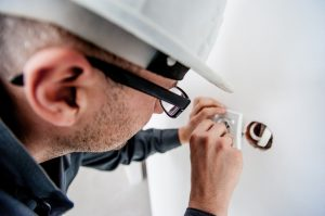 Électricien travaillant sur une prise électrique, touchant les fils électriques
